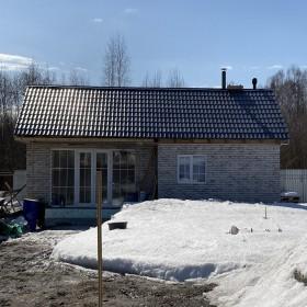 """Фасад частного дома облицован термопанелями ТПК """"ЕВРОФАСАД"""" серый с керамогранитом."""